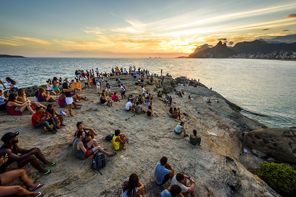 Locals and tourists watching the sunset from Arpoador Rock in Ipanema Beach, Rio de Janeiro, Brazil