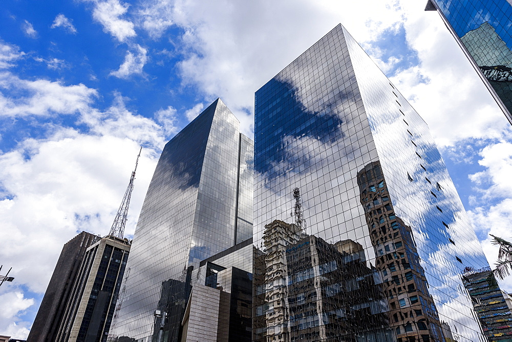 Clouds reflected on tall commercial buildings in Avenida Paulista, central São Paulo, Brazil