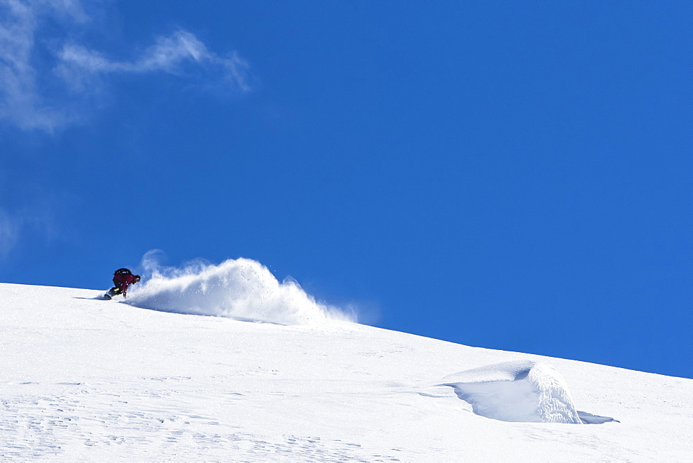 Professional Snowboarder Helen Schettini, rides fresh powder on a sunny day while snowboarding in Haines, Alaska.