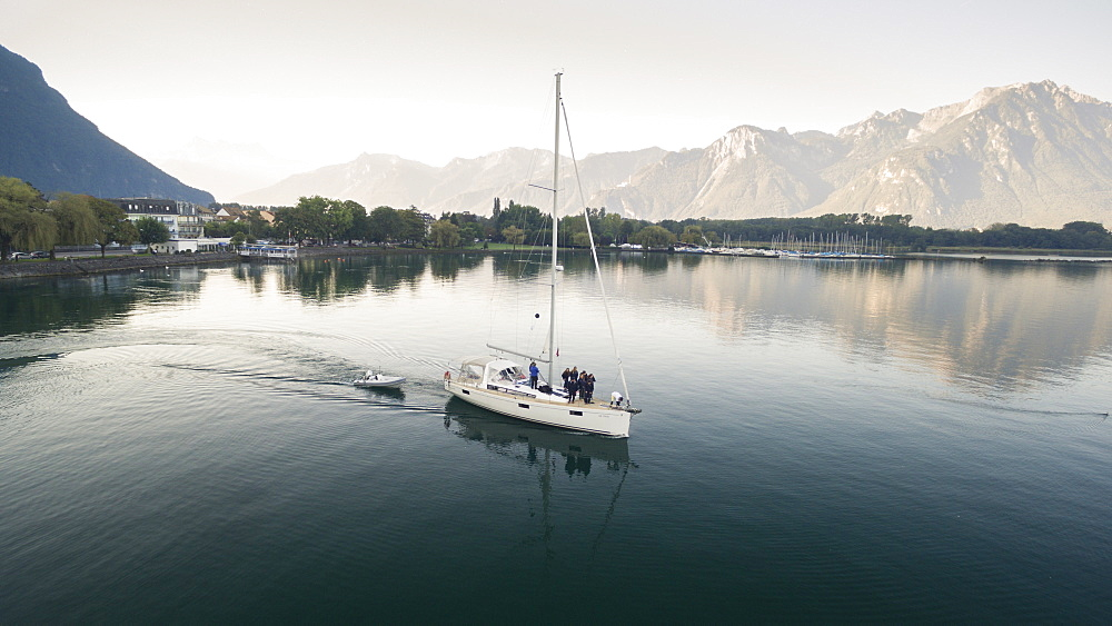 aerial view on a sailing boat and rescue boat crossing the Geneva Lake, with mountains in the background, trees on the lake's banks and a marina in Villeneuve, Vaud Canton, Switzerland