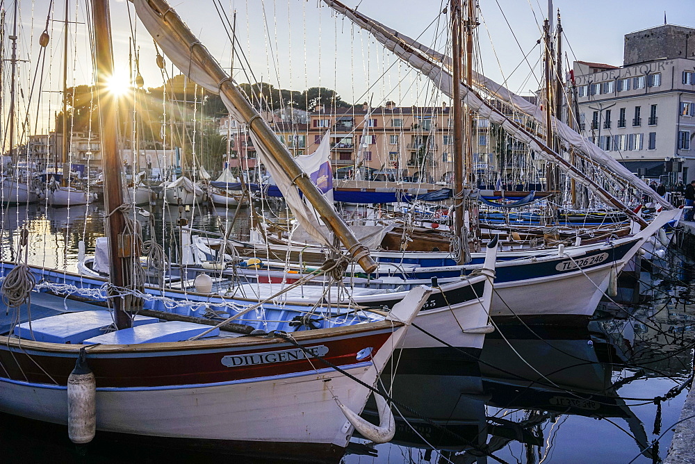 winter sunset over the harbor of Sanary-sur-Mer in the South of France with several boats docking, among which three wooden boats in the foreground of the picture.