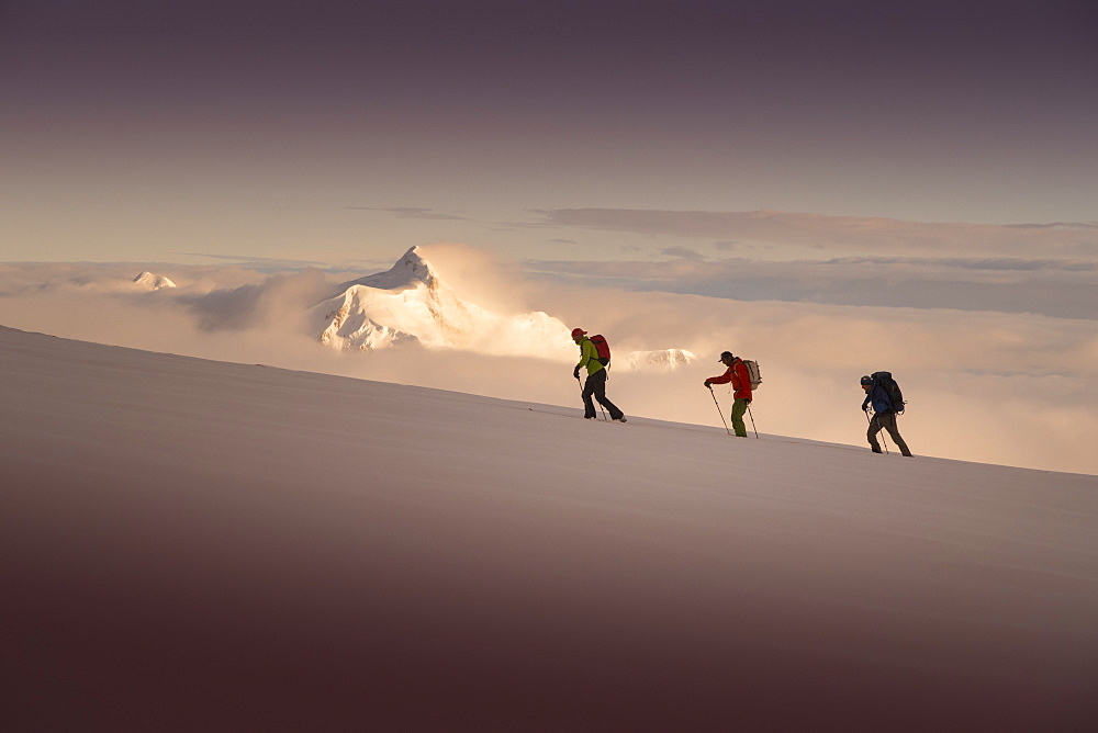 Three ski mountaineers ascending Denali, with sunset over Mount Hunter in the background. Denali National Park is a great location for backcountry skiing and mountain climbing tours.