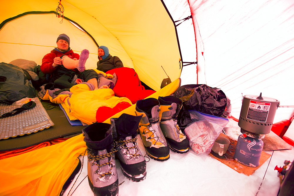 Two mountaineers are laying inside a tent at High Camp on Denali in Alaska. Early morning they are going for a summit push to the highest mountain of Northern America.