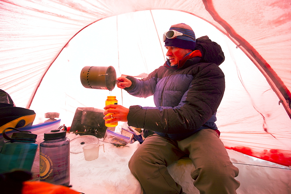 A mountaineers is melting snow to get drinking water, inside a tent at High Camp on Denali in Alaska. Early morning they are going for a summit push to the highest mountain of Northern America.