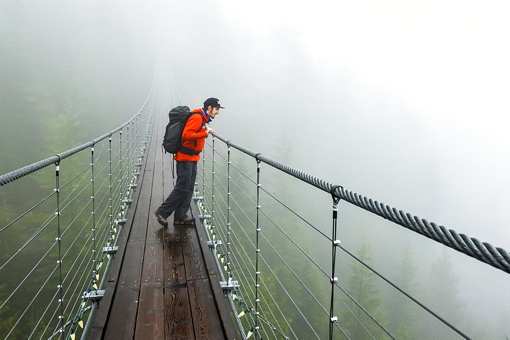 A man looks over a suspension bridge on a rainy fall day in Squamish, British Columbia.