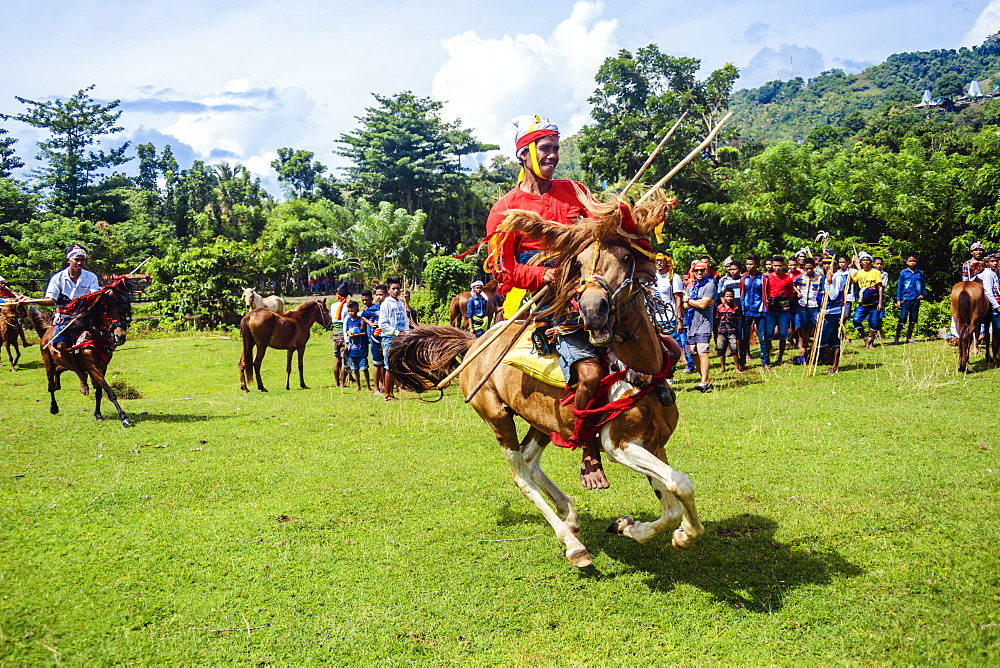 Young man wearing traditional costume riding horse and holding spear at Pasola Festival, Sumba island, Indonesia