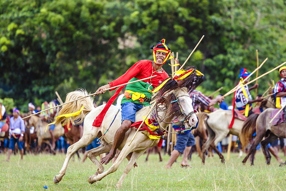 Man riding horse with spear and competing at Pasola Festival, Sumba island, Indonesia
