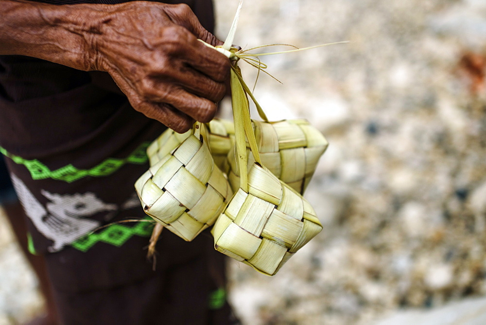 Hand holding traditional baskets of rice, Sumba Island, Indonesia