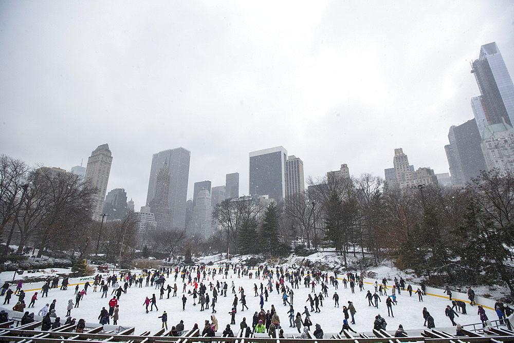 Crowd of people ice skating on Wollman Rink in Central Park in New York City during the winter, USA