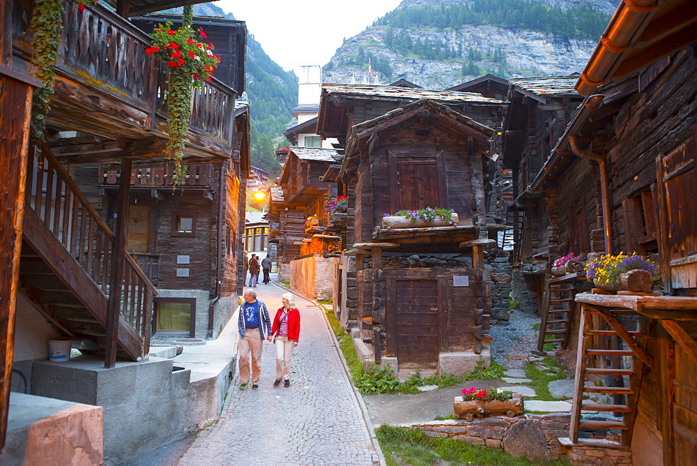 Narrow street with old wooden houses in historical part of Zermatt, Valais, Switzerland