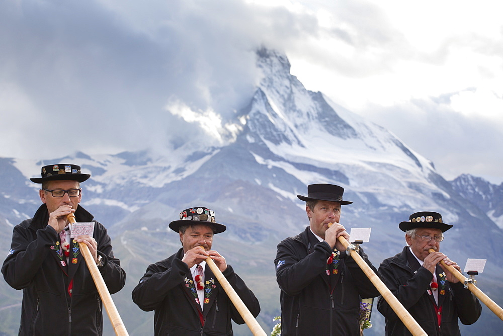 Four traditionally dressed locals playing alphorn against Matterhorn mountain, Zermatt, Valais, Switzerland