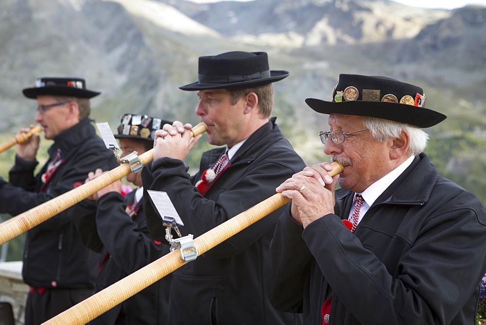 Four traditionally dressed locals playing alphorn, Zermatt, Valais, Switzerland