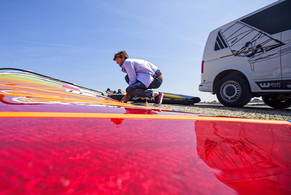 Pierre Le Coq preparing his windsurfing gear on a jetty near his van at Plouguerneau, Brittany, France. - 857-94863