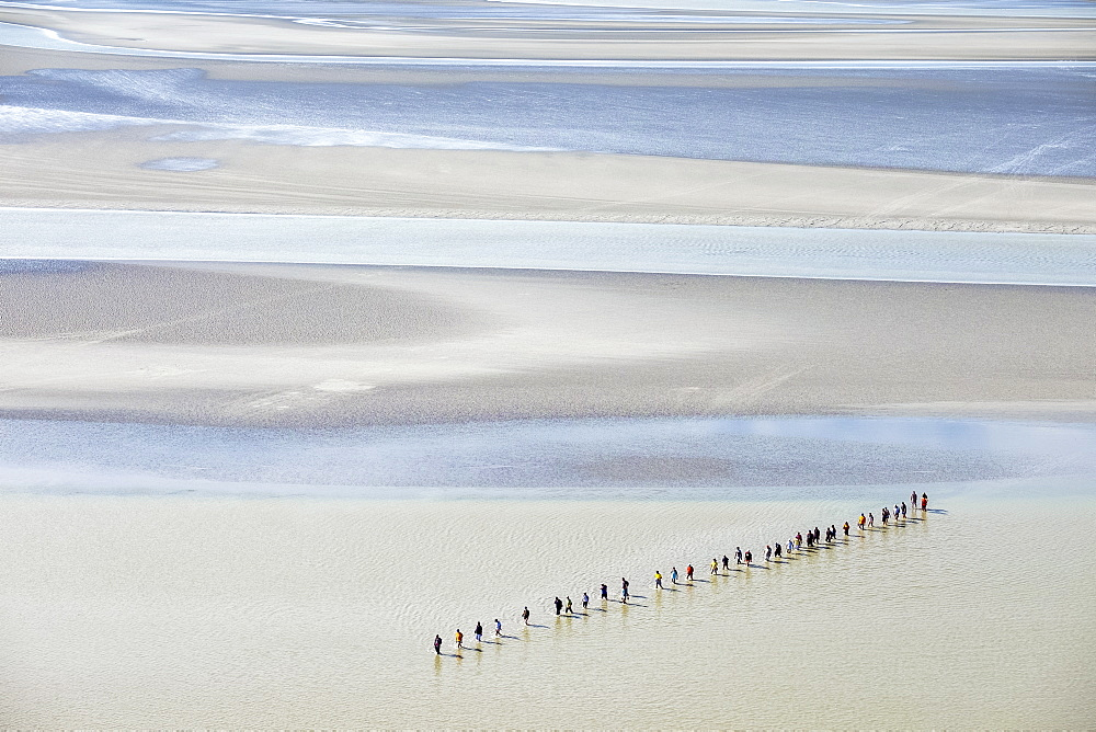 People walking through mudflats at low tide, Normandy, France