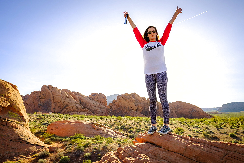 Woman standing in celebratory pose, Valley of Fire State Park, Nevada, USA