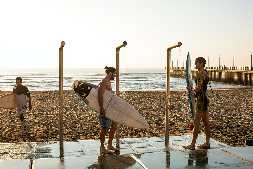 Men washing down surfboards near promenade on Golden Mile in Durban, South Africa