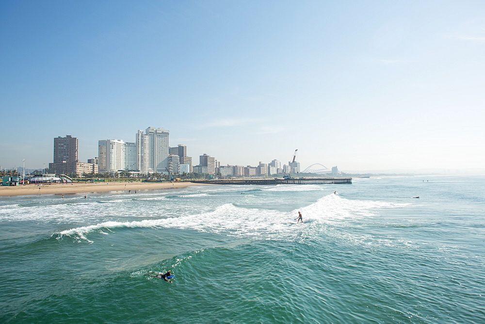 Surfers riding waves near pier on Golden Mile with skyline of Durban, South Africa