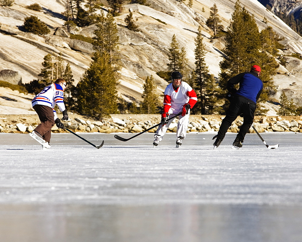 People playing ice hockey on a frozen, snow free Tenaya Lake in Yosemite National Park.