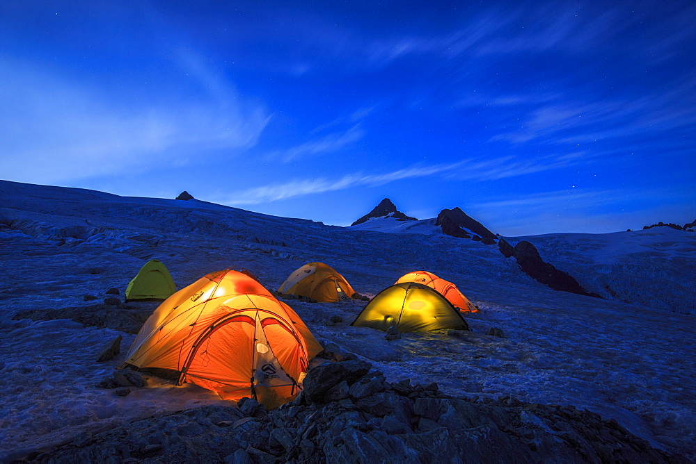 Glacier campsite with illuminated tents at Mount Shuksan, North Cascades National Park, Washington State, USA
