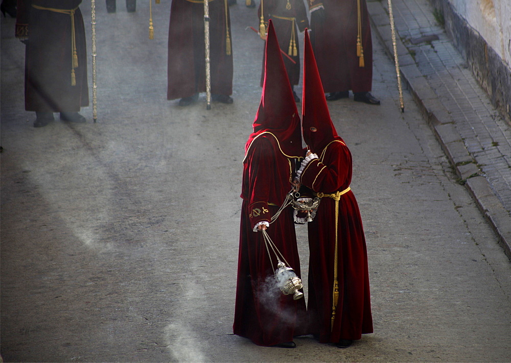 Altar servers wearing red clothing and pointed hoods talking during Easter Week celebrations in Baeza, Jaen Province, Andalusia, Spain