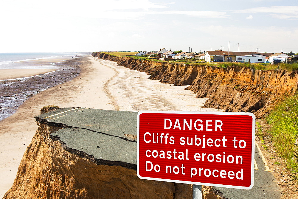 A collapsed coastal road at between Skipsea and Ulrome on Yorkshires East Coast, near Skipsea, UK. The coast is composed of soft boulder clays, very vulnerable to coastal erosion. This section of coast has been eroding since Roman times, with many villages having disappeared into the sea, and is the fastest eroding coast in Europe. Climate change is speeding up the erosion, with sea level rise, increased stormy weather and increased heavy rainfall events, all playing their part. - 857-95431