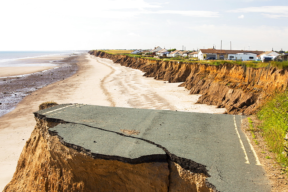 A collapsed coastal road at between Skipsea and Ulrome on Yorkshires East Coast, near Skipsea, UK. The coast is composed of soft boulder clays, very vulnerable to coastal erosion. This section of coast has been eroding since Roman times, with many villages having disappeared into the sea, and is the fastest eroding coast in Europe. Climate change is speeding up the erosion, with sea level rise, increased stormy weather and increased heavy rainfall events, all playing their part. - 857-95432
