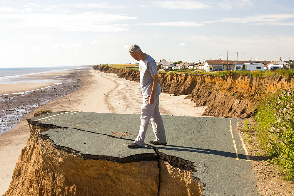 A collapsed coastal road at between Skipsea and Ulrome on Yorkshires East Coast, near Skipsea, UK. The coast is composed of soft boulder clays, very vulnerable to coastal erosion. This section of coast has been eroding since Roman times, with many villages having disappeared into the sea, and is the fastest eroding coast in Europe. Climate change is speeding up the erosion, with sea level rise, increased stormy weather and increased heavy rainfall events, all playing their part.