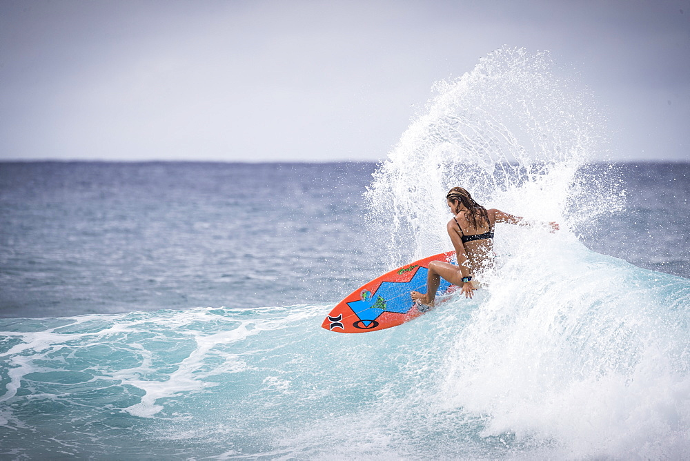 Rear view of single female surfer in bikini riding wave in sea