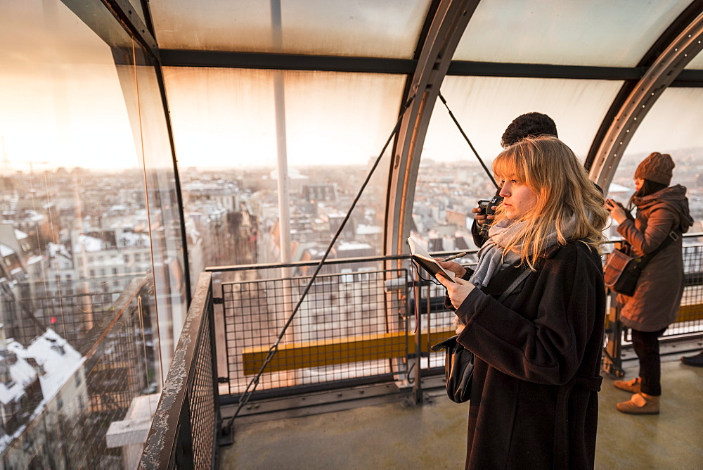 Tourists looking through window at view of Paris, France in Centre Georges Pompidou at sunset - 857-95464