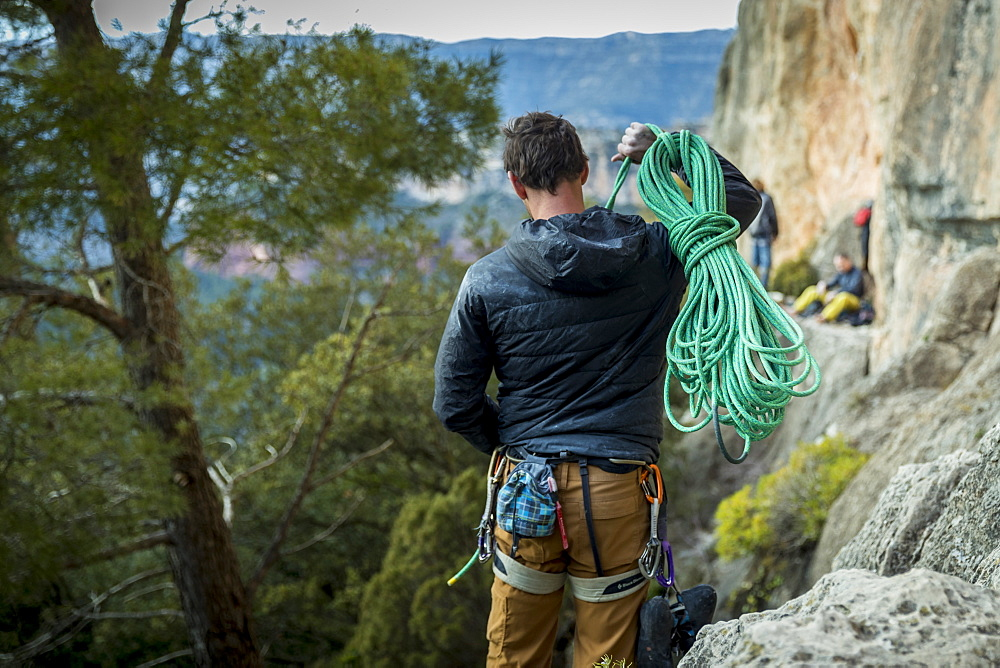 Rear view shot of male rock climber carrying rope to cliff, Siurana, Catalonia, Spain