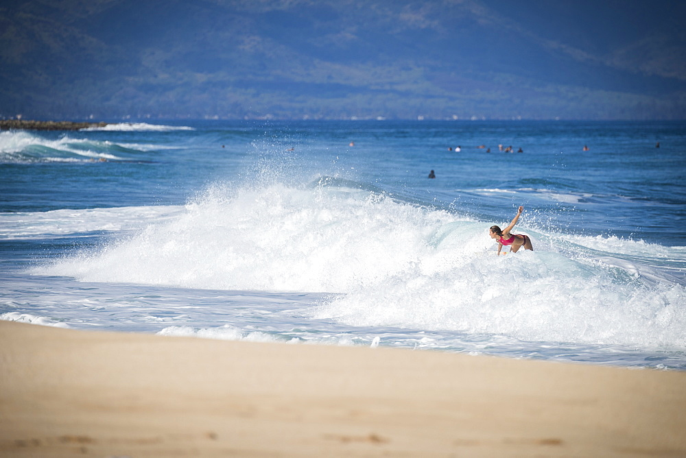 Distant view of female surfer surfing near beach