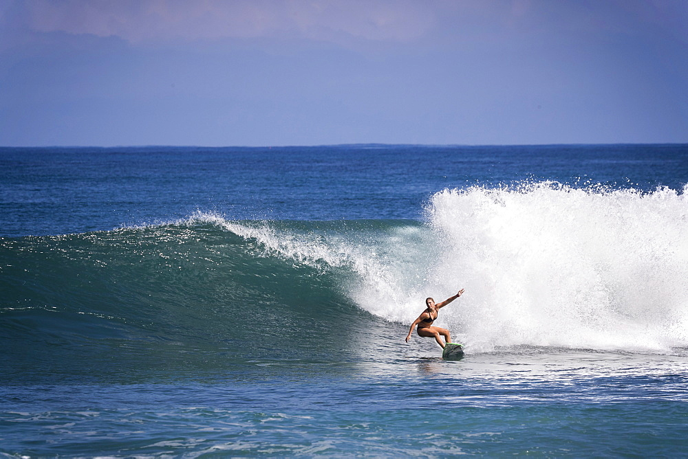 Distant view shot of single woman in bikini surfing in sea - 857-95477