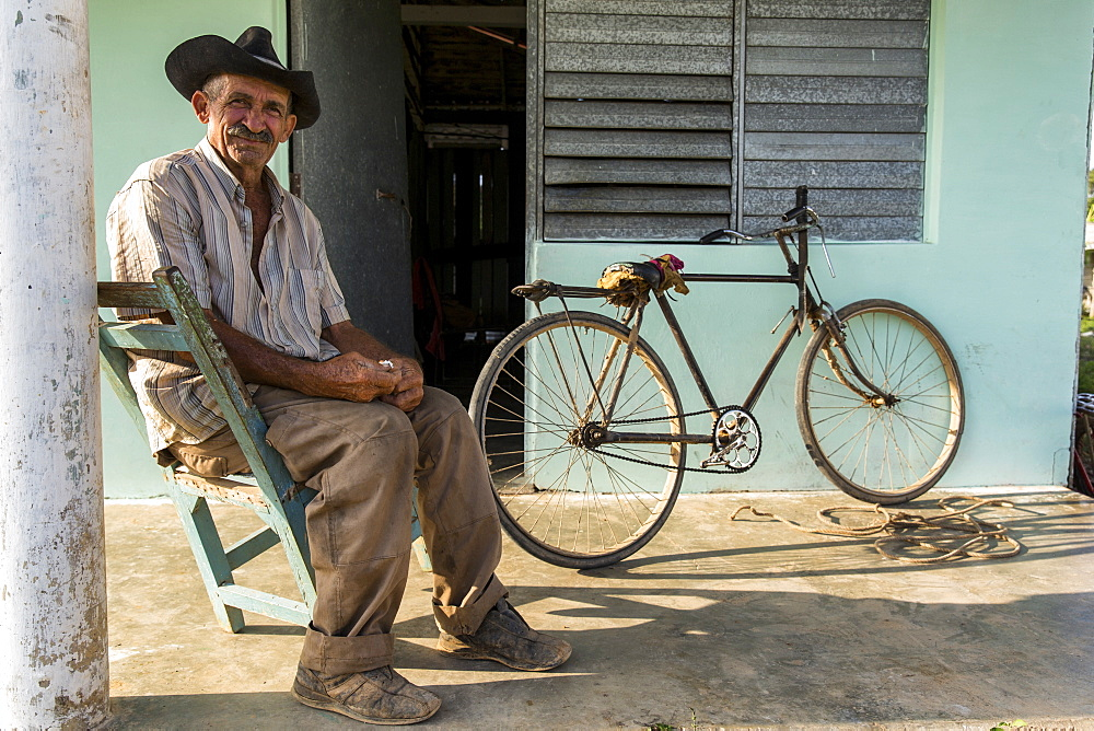 Man sitting in chair and posing for portrait outside home, Vinales, Pinar del Rio Province, Cuba
