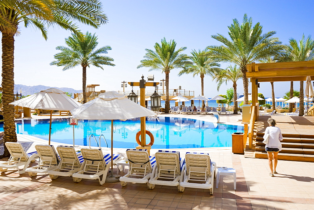 Woman walking by pool in tourist resort with palm trees, Aqaba, Jordan - 857-95512