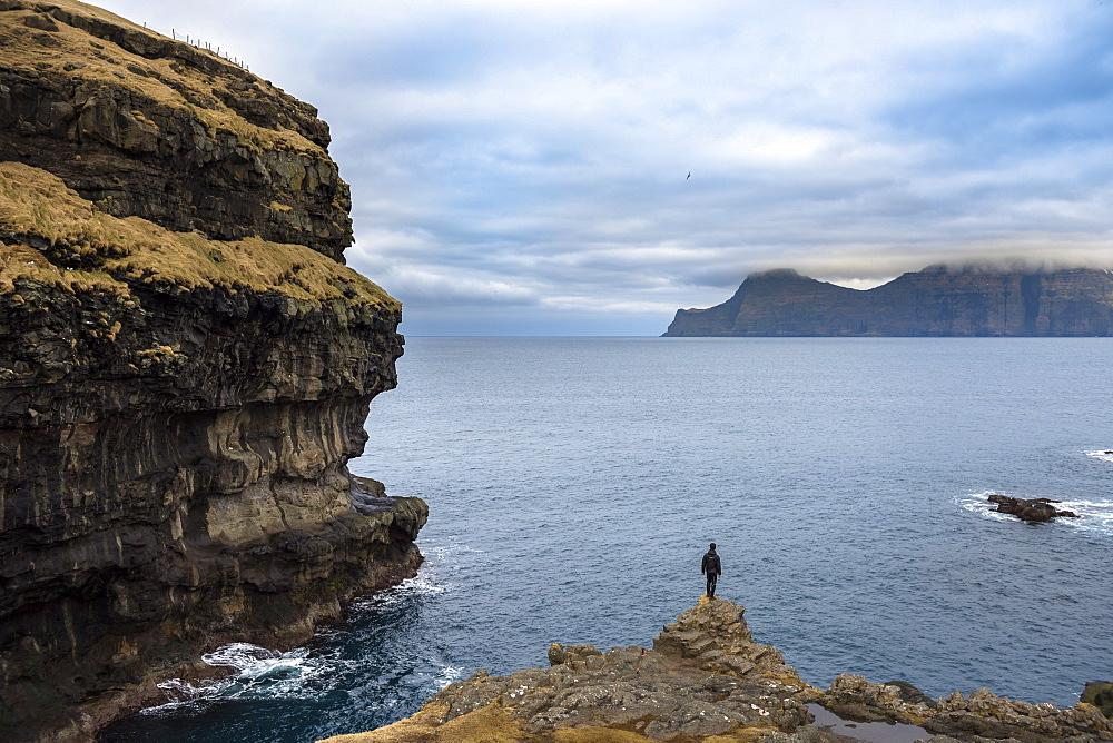 Rear view of man standing on seashore, Faroe Islands, Denmark - 857-95518
