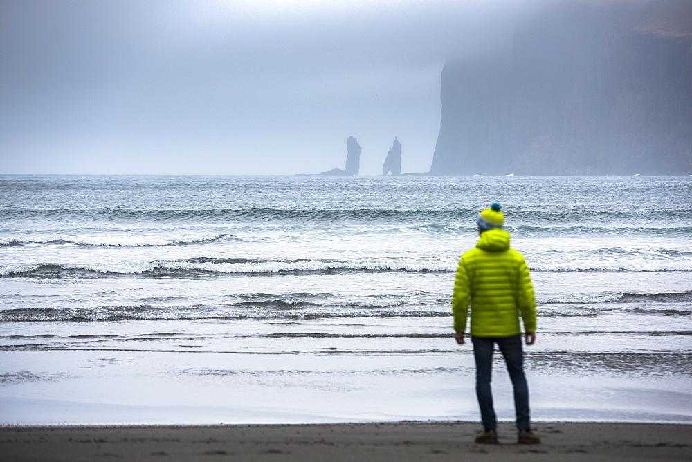 Rear view of man standing on seashore, Faroe Islands, Denmark