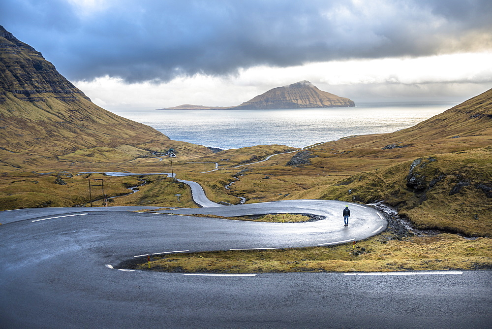Distant view of man walking on winding road on seashore, Faroe Islands, Denmark