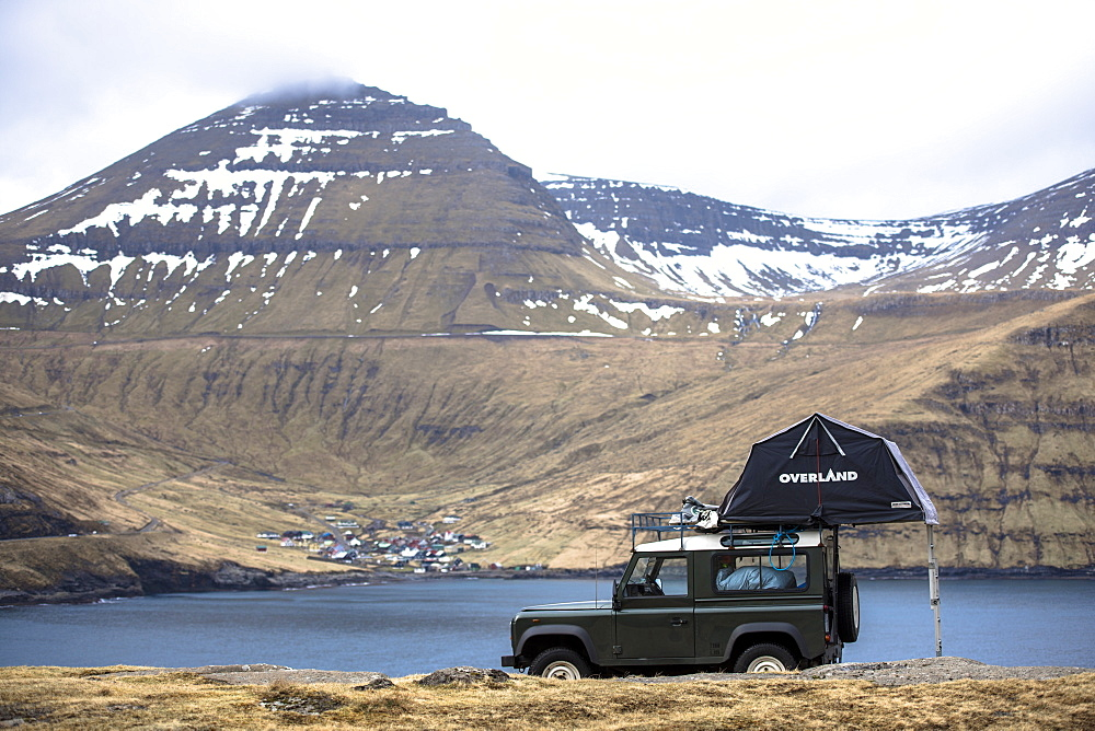 Side view of single 4x4 car with tent parked against mountains, Faroe Islands, Denmark
