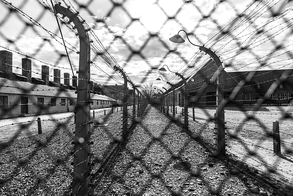 Barbed wire lines a corridor behind a chain link fence at the Auschwitz concentration camp in Oswiecim, Malopolskie Province, Poland