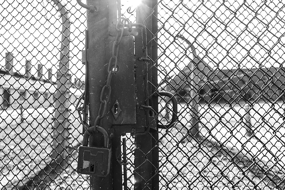 A metal chain and pad lock secure a chain link fence as the sun bursts through a crack at the Auschwitz concentration camp in Oswiecim, Malopolskie Province, Poland