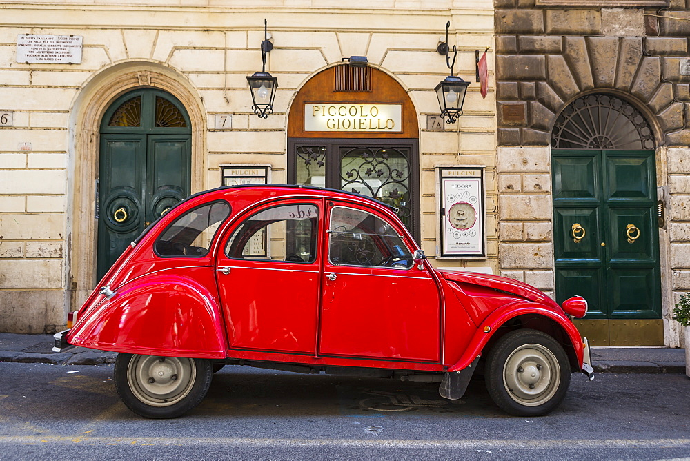 Side view shot of single red vintage car parked on street, Rome, Italy
