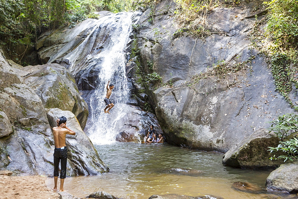 Shirtless boy jumping off rock at waterfall, Chiang Rai, Thailand