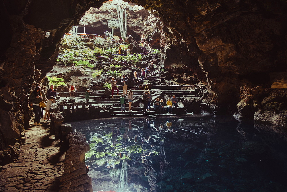 Tourist visiting cave and lake inside Jameos del Agua, Lanzarote, Canary Islands, Spain