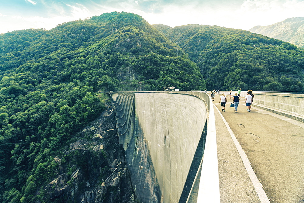 Landscape with forest and tourists walking on Verzasca Dam, Verzasca, Ticino, Switzerland
