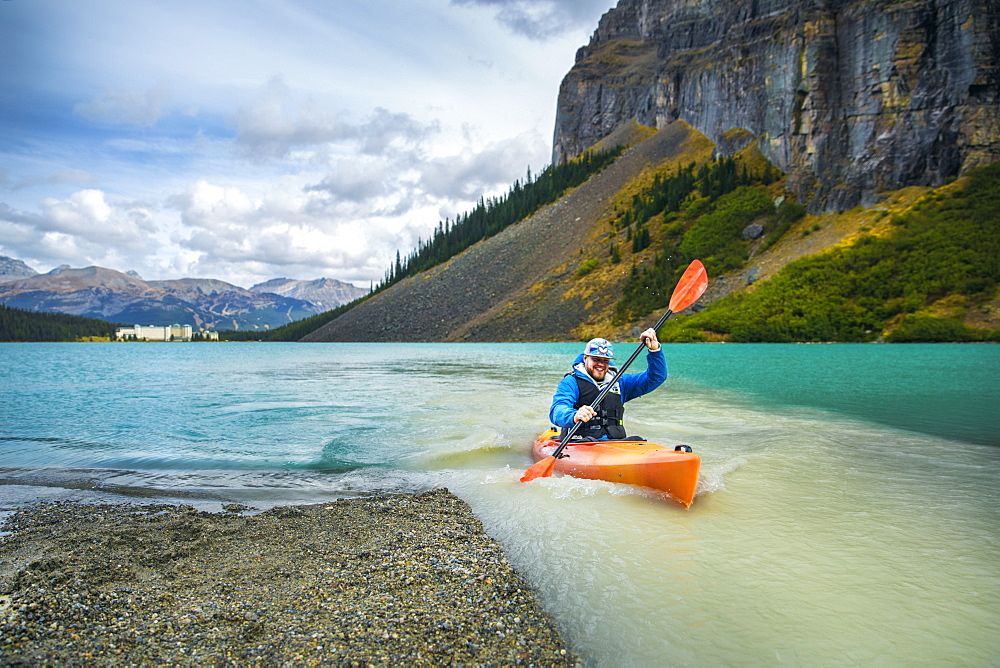 Male kayaker paddling by riverbank on glacial river, Lake Louise, Alberta, Canada