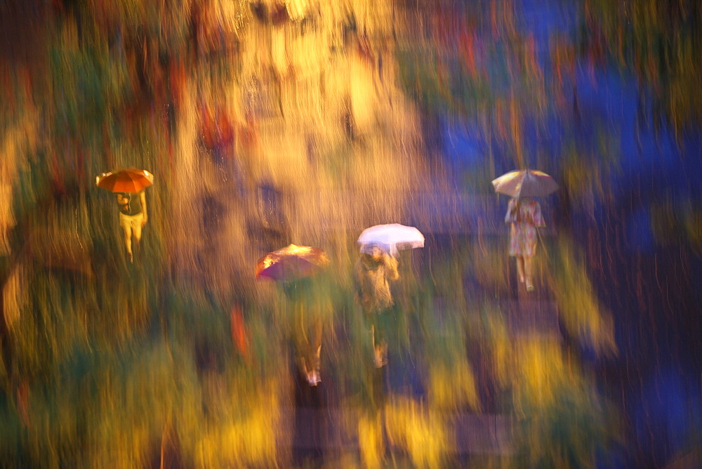 Blurred image of people walking in rain in Central Park, New York City, New York, USA