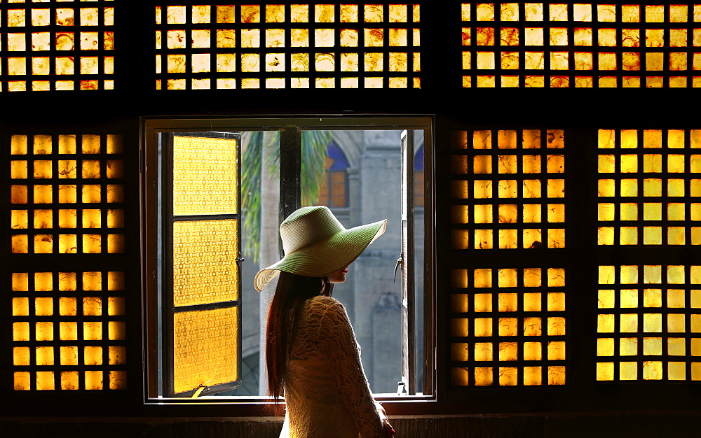 Woman in white lace dress and hat in hallway in front of capiz (shell) window in San Agustin Church, Manila, Philippines
