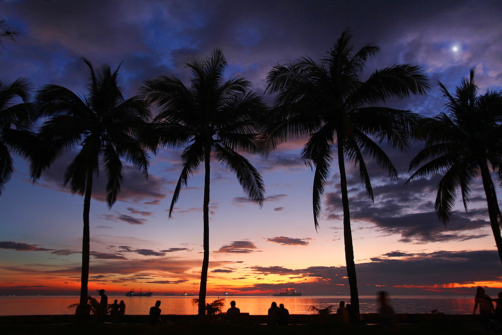 Silhouettes of people and palm trees against sky and sea at sunset, Manila, Philippines