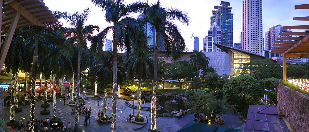 Palm trees and people in Greenbelt Park in city of Makati, Philippines