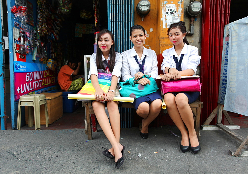 Group of three female students sitting and looking at camera in Manila, Philippines